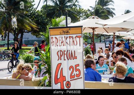Miami Beach Florida Ocean Drive New Year's Day Art Deco District Cafe Medi sidewalk cafe restaurant business umbrellas alfresc - Stock Image