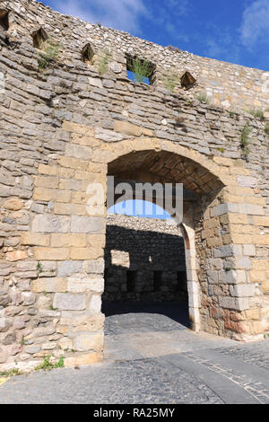 A gateway arched entrance over a cobbled street through the city wall of the medieval city of Morella, CAstellon, Valencia, Spain - Stock Image