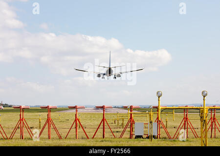 Passenger aircraft landing on runway - Stock Image
