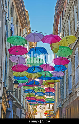 Colourful umbrellas hanging between buildings above a street in the old city area in Beziers, France - Stock Image