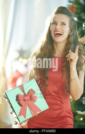 happy young woman in red dress with green Christmas present box got idea near Christmas tree - Stock Image