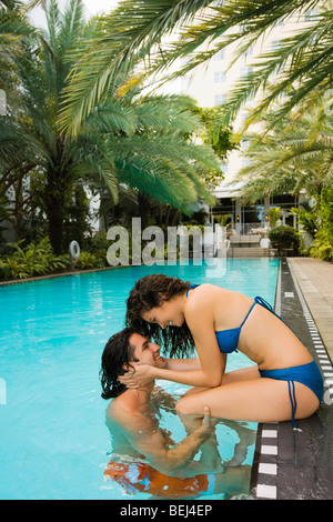 Young couple romancing at poolside - Stock Image
