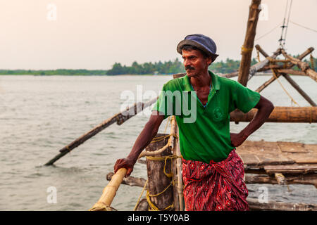 COCHIN, INDIA - MARCH 13, 2012: Unidentified fisherman and chinese fishing nets in Fort Kochi in Cochin, India - Stock Image