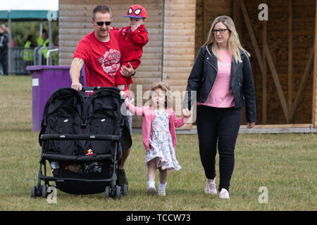 A family walking together in the park with the dad carrying a baby and pushing a double pushchair - Stock Image