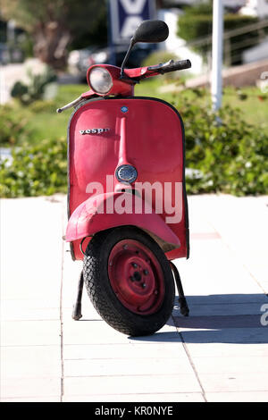 An old, well used Vespa scooter. The scooter has been well used and hand painted with red paint that's faded - Stock Image