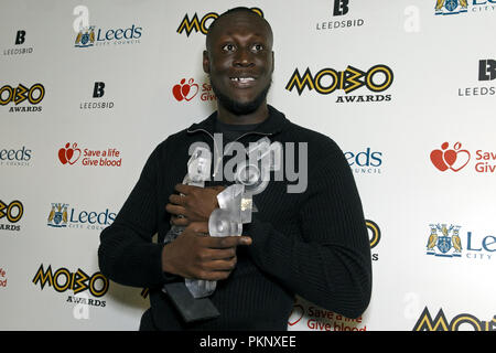 Stormzy posing with his three MOBO trophies at the 2017 MOBO Awards on 29 November 2017. Stormzy won the MOBOs for Best Album (Gang Signs & Prayer), Best Male Act and Best Grime Act. - Stock Image