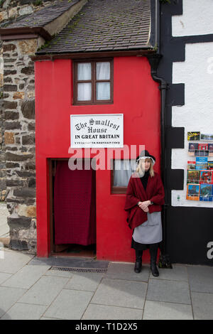 Lady dressed in traditional Welsh costume standing outside the smallest house in Great Britain at Conwy in North Wales - Stock Image