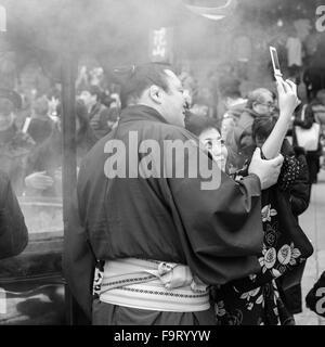 Sumo wrestler Asahishou (旭日松) visiting the Sensō-ji temple (金龍山浅草寺) in Asakusa, Tokyo with his young lady, taking - Stock Image