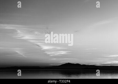 Beautiful view of Trasimeno lake (Umbria, Italy) at sunset, with cloud shapes on the sky - Stock Image
