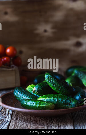 Plate of freshly picked organic cucumbers, cherry tomatoes on rustic  table, plant based food, close up, selective focus - Stock Image