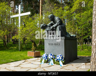 The monument of the fallen in Finland's wars at the cemetery of Kuopio, with wreaths of the Memorial Day placed in front of the sculpture. - Stock Image