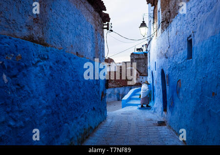 Chefchaouen, Morocco : A senior Riffian woman walks along a blue-washed alley in the medina old town. - Stock Image