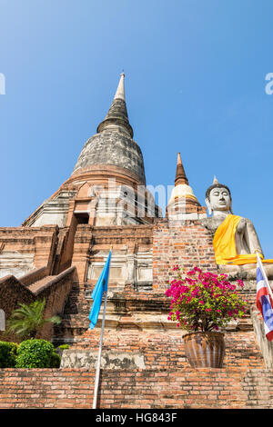 Buddha statue at the bottom of a large ancient pagoda on blue sky background at Wat Yai Chai Mongkon temple in Phra - Stock Image