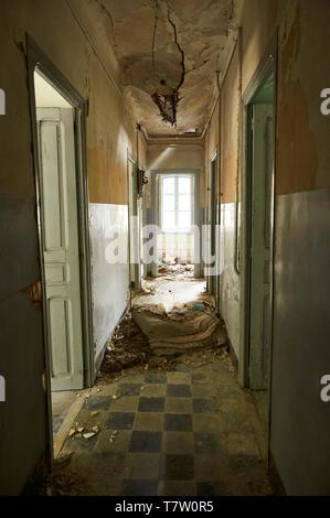 Interior corridor in ruined facilities at the abandoned Canfranc International railway station (Canfranc, Pyrenees, Jacetania, Huesca, Aragon, Spain) - Stock Image