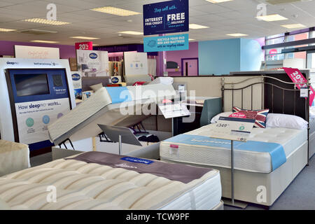 Interior of bedding store with displays of beds, UK - Stock Image