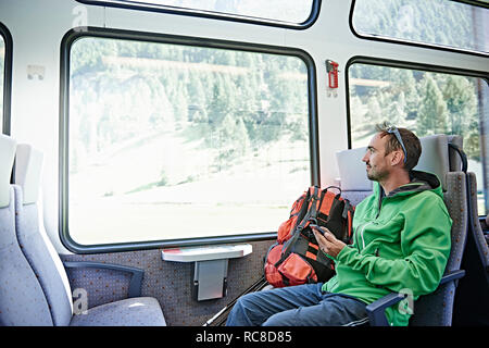 Hiker in train, Valais, Switzerland - Stock Image