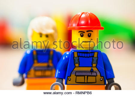 Poznan, Poland - February 13, 2019: Lego construction worker with satisfied emotion standing in front of other worker with long hair in soft focus bac - Stock Image