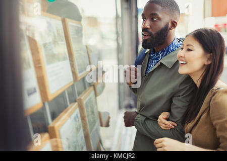 Young couple browsing real estate listings at storefront - Stock Image