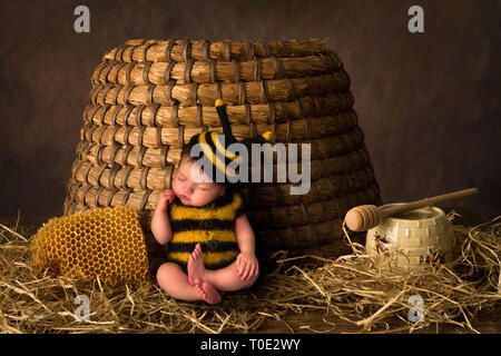 Sleepy cute baby in bee outfit resting against an antique beehive - Stock Image