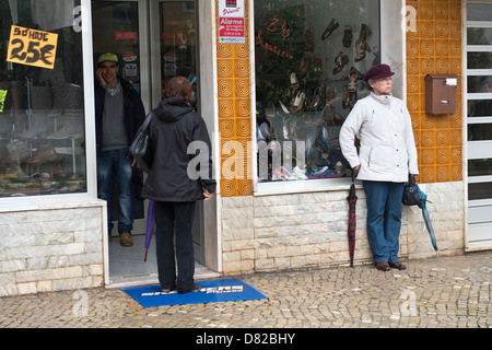 People at the shop entrance Easter Sunday in São Brás de Alportel Algarve Portugal Mediterranean Europe - Stock Image
