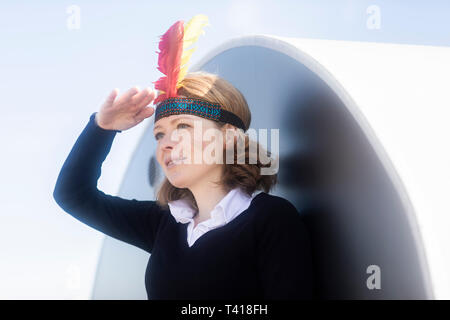 Woman dressed up in North American tribal costume shielding her eyes, Germany - Stock Image