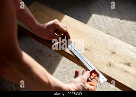 Man measuring a plank of wood using a metal ruler. - Stock Image