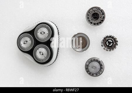 Replacement cutting head and cutters for a Philips electric shaver showing old and new replacements - Stock Image