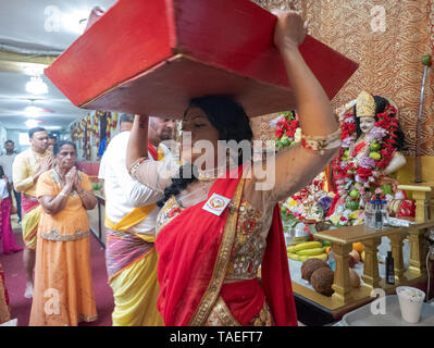 At her mother's (orange)  thanksgiving service a young Hindu woman brings offerings to the deities at a temple in Ozone Park, Queens, New York City. - Stock Image