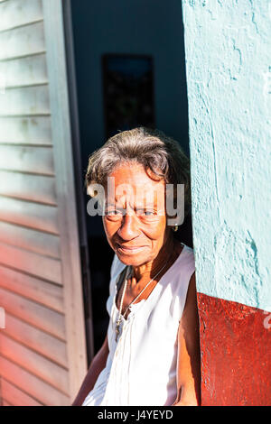 Old Cuban lady in doorway, looking sad, Cuban poverty, Afro Cuban lady woman, old lady in Cuba - Stock Image