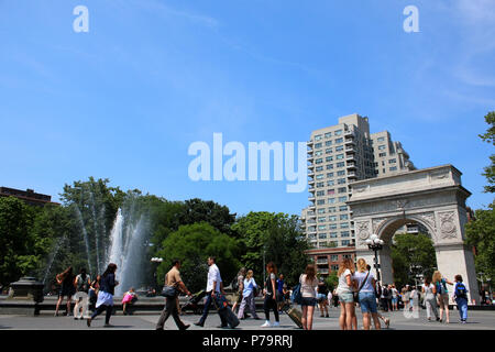 NEW YORK, NY - JUNE 15: People gathered near Washington Square Park fountain on hot summer day, West Village, Manhattan on JUNE 15th, 2017 in New York - Stock Image
