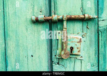 Old, weathered green door - Stock Image