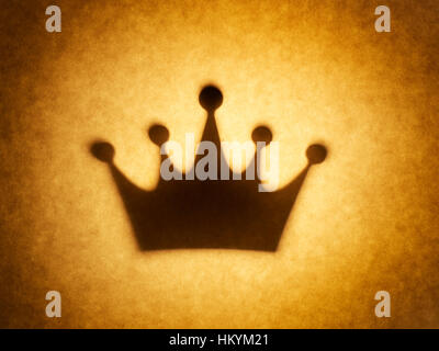 Backlit silhouette of crown shape cut out against brown tone paper, with spot highlight. - Stock Image