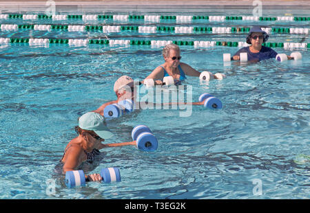 Senior women & man attending water aerobics class, working with 'water dumbbells', outdoor public heated swimming pool. - Stock Image