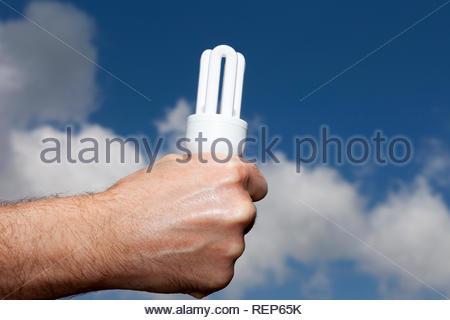 Energy Saving light bulb against a sky background - Stock Image