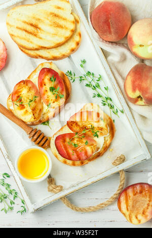 Gourmet summer Breakfast - sandwiches (bread toast, bruschetta) with grilled peaches, cream cheese (ricotta, mascarpone), thyme and honey on an old wh - Stock Image