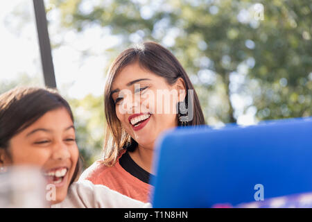 Happy mother and daughter using laptop - Stock Image