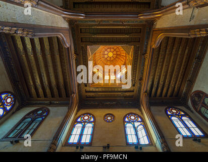Wooden decorated dome mediating ornate ceiling with floral pattern decorations at al Ghuri Mausoleum, Cairo, Egypt - Stock Image