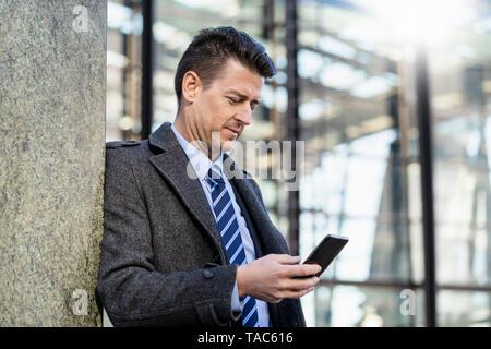 Businessman leaning against a wall using cell phone - Stock Image