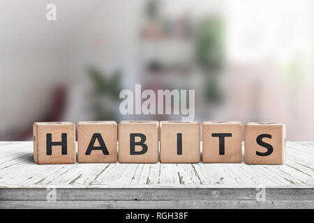What is your habits? Sign with the word habits on a wooden desk in a bright room - Stock Image