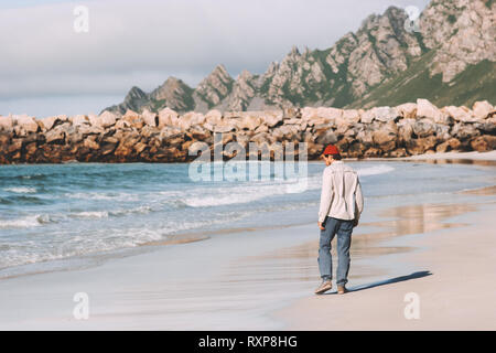 Man walking alone on empty beach traveling in Norway active vacations outdoor lifestyle adventure weekend trip - Stock Image