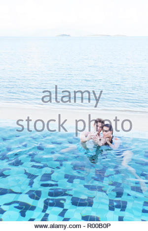Young couple taking selfie in swimming pool - Stock Image