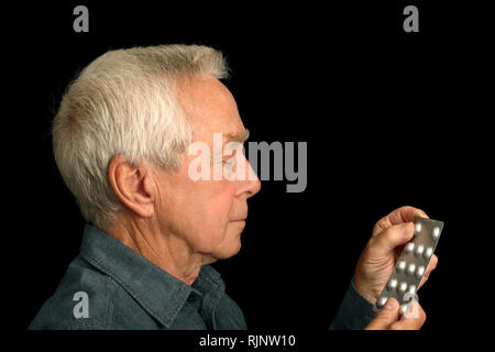 A man in his 60's about to take a tablet from a bubble pack - Stock Image
