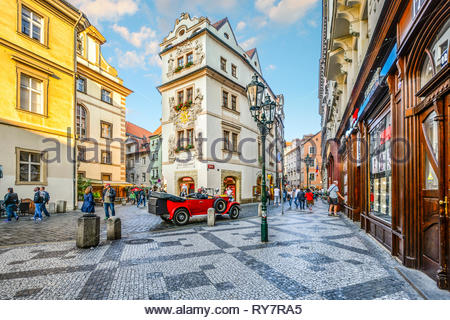 Tourists pass by shops and cafes in a picturesque section of Old Town Prague, Czech Republic. - Stock Image
