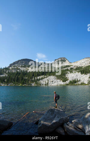 Photograph of a young backpacker on the shore of Beehive Lake while on a hiking trip, Selkirk Mountains, Sandpoint, Idaho, USA - Stock Image