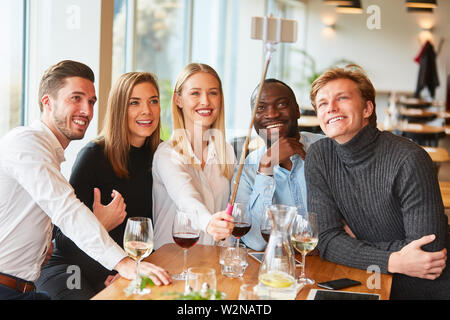 Young people as friends in the restaurant take self portrait with the selfie stick - Stock Image