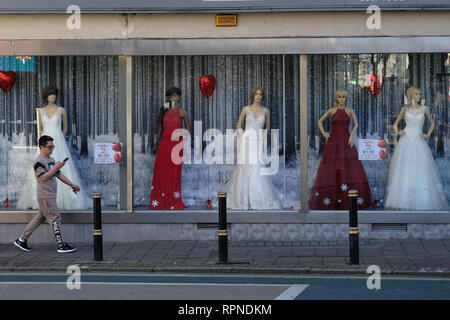 A man walks past a wedding dress shop in Exeter, UK. - Stock Image