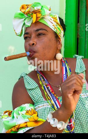 Cigar smoking lady  posing for tourists  in a door way  near Convento de San Francisco de Asís in Old Havana - Stock Image