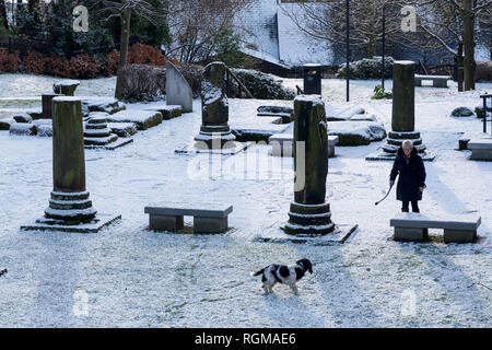 Chester, Cheshire, UK. 30th December 2018. A woman exercising her dog in the snow covered Roman Gardens in the city centre. Credit: Andrew Paterson/Alamy Live News - Stock Image