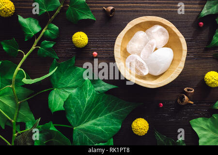 Polished Clear Quartz with Ivy and Craspedia on Dark Wood - Stock Image