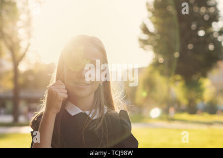 Portrait of european cute teen girl with maple leaf in her hands. She poses in sunset and smiles at camera. Sheet closes one eye - Stock Image